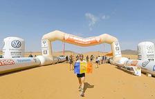 Jordi Buj creuant la meta de l'última etapa de la marató des Sables amb la bandera tricolor.