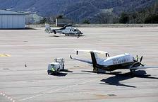 Un avió i un helicòpter a la pista d'enlairament de l'aeroport Andorra-Pirineus.