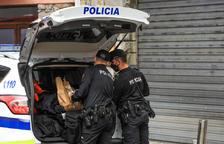 Dos agents de policia revisant el maleter del cotxe patrulla.