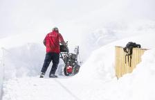 Un treballador treu neu en una estació d'esquí.