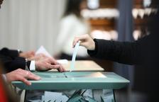 Una persona diposita el seu vot en una urna.