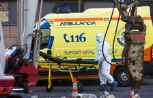Un professional sanitari arrossega una llitera a l'exterior de l'hospital.