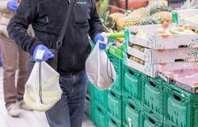 Un consumidor amb dos cistells de fruita.