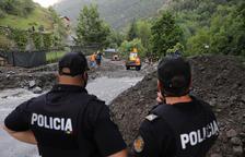 Dos agents de policia observant els treballs per retirar la terra i pedres arrossegades.
