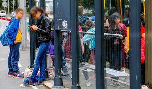 Dos joves esperant en una parada de bus.