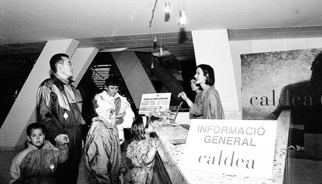 Una família de turistes informant-se a la recepció de Caldea, el dia de l'obertura.