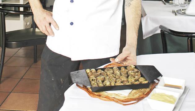 El cuiner Paulo García mostra uns cargols del país a la llauna