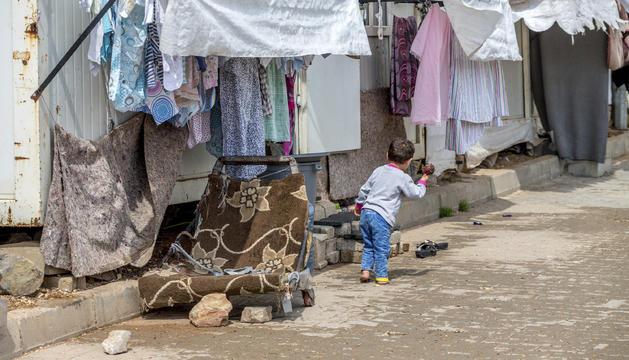 Un nen refugiat jugant a l'entrada de casa seva.
