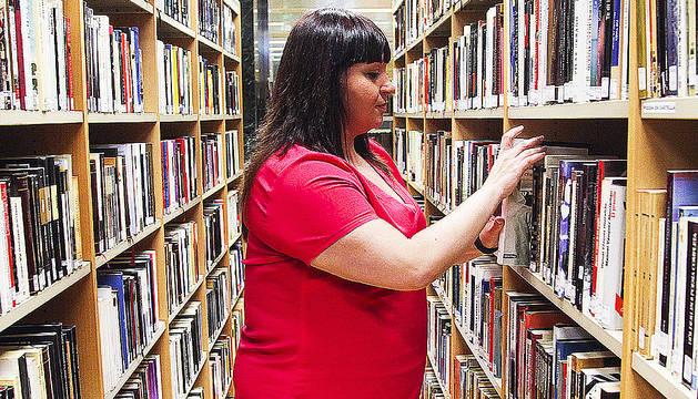 Una usuària busca un llibre a la biblioteca de Sant Julià.