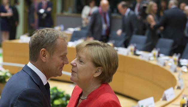 Angela Merkel i Donald Tusk se saluden, ahir durant el Consell Europeu a Brussel·les.