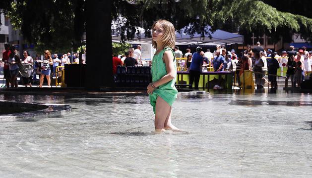 Una nena es refresca a l'aigua.