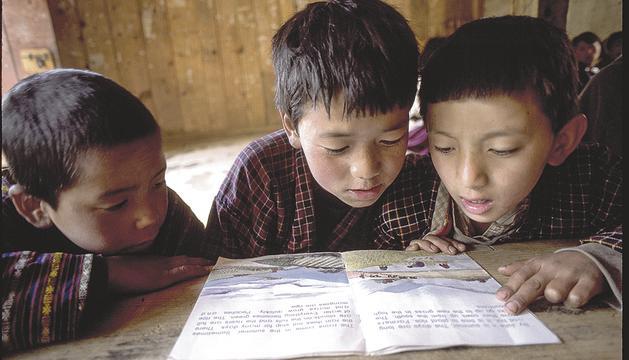Tres nens de Bhutan llegeixen en una escola