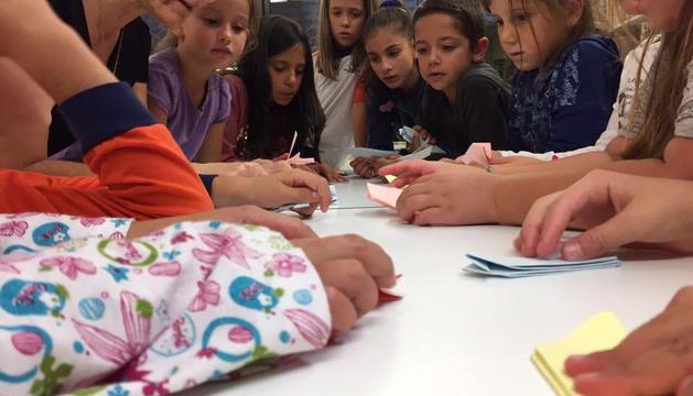 Els alumnes del taller aprenen a fer coloms d'origami.