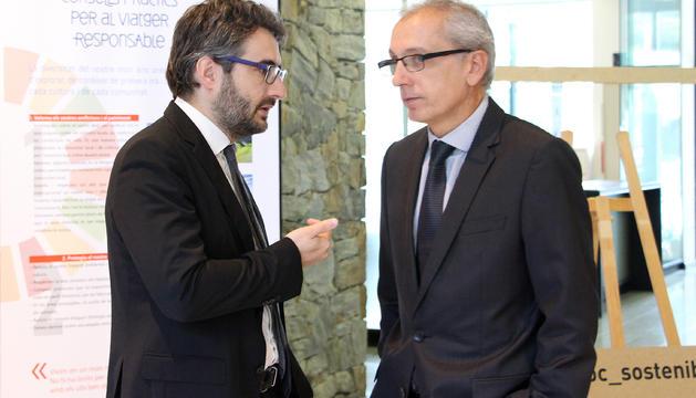 El ministre d'Educació i Ensenyament Superior, Eric Jover, i el ministre de Turisme, Francesc Camp, conversen durant l'exposició inaugurada avui a Aixovall.