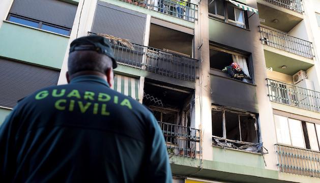 Dos bombers treballant a l'edifici incendiat.
