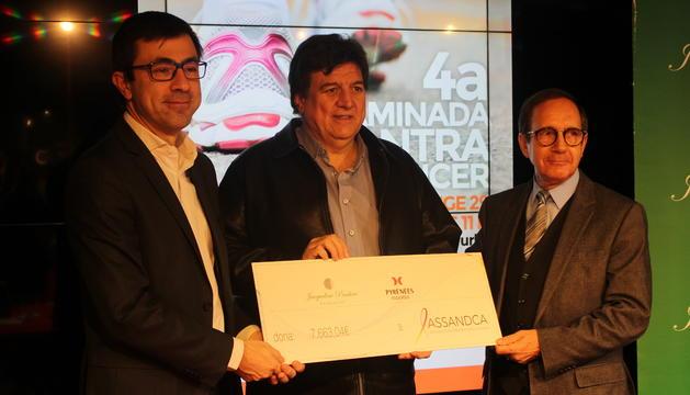 El director de marqueting de Pyrénées SA, Joaquim Serrahima, i el representant de la Fundació Jacqueline Pradère, Josep Manzano, fan entrega de la recaptació de la caminada contra el càncer al president d'Assandca, Josep Saravia.