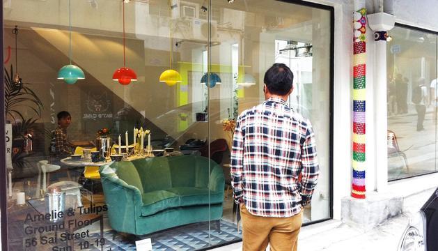 Un home mirant l'aparador d'una botiga.