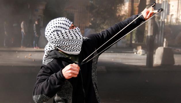 Un palestí llançant una pedra contra l'exèrcit israelià.