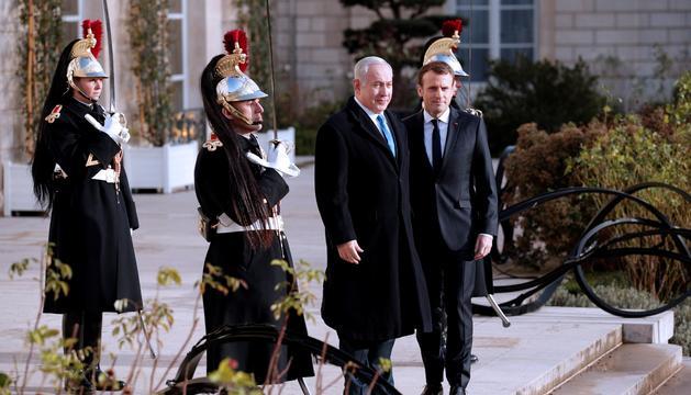 El president francès saludant el primer ministre israelià, Benjamin Netanyahu, a l'arribada a l'Elisi.