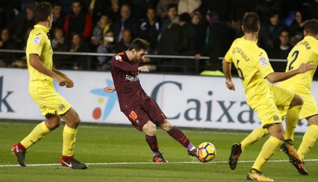 Leo Messi xuta sota la mirada de tres defenses del Vila-real.