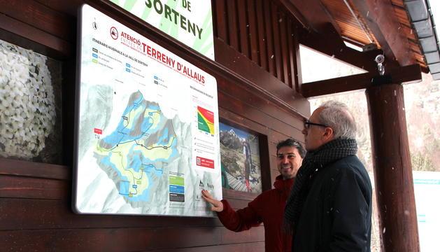 El cap d'àrea de Medi Físic del Cenma, Marc Pons, i el ministre de Turisme, Francesc Camp, consulten un dels panells.
