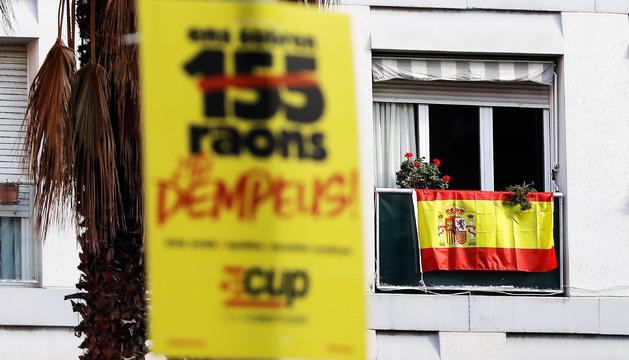 Un cartell electoral de la CUP en un arbre i al fons una bandera espanyola en un balcó.