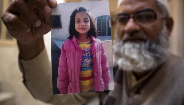 El pare ensenya la foto de la nena de set anys assassinada i violada.