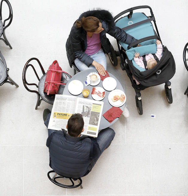 Una parella a una terrassa prenent un café, amb un cotxet de bebé
