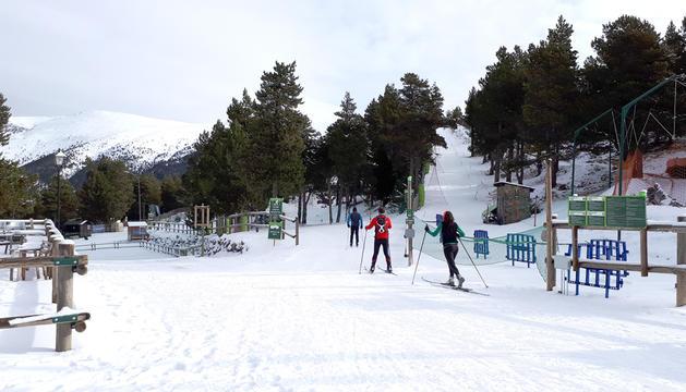 Usuaris del parc fent esquí de fons.