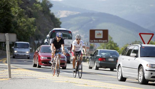 Una parella de ciclistes transitant per l'N-152 a la Seu d'Urgell.
