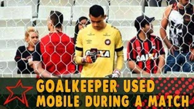 Un porter de futbol es posa a mirar el mòbil mentre s'està disputant el partit