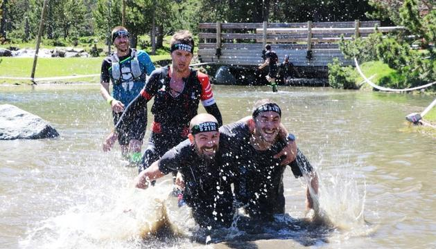 Diversos espartans durant la primera jornada de l'Spartan Race Andorra-Encamp superant un obstacle d'aigua.