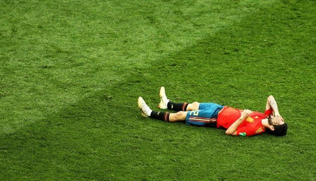 Isco, estirat damunt el terreny de joc, es lamenta de l'eliminació d'Espanya del Mundial.