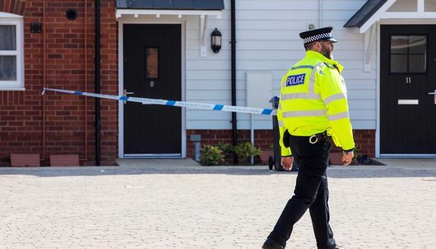 Un agent de policia davant de la casa on es va localitzar la parella intoxicada.