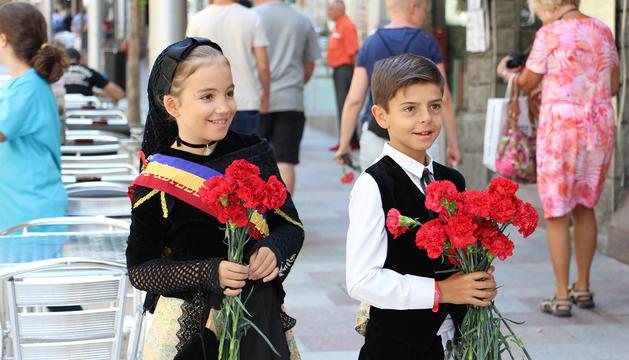 Irene Denuzzo, pubilleta, i Adrià Llobet, hereuet, amb els clavells vermells que han repartit als turistes.