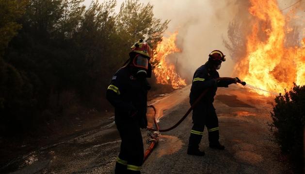 Els bombers intenten extingir l'incendi a Penteli, al nord d'Atenes.