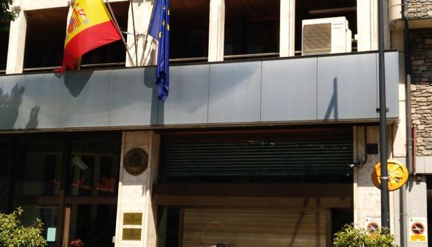 Un operari esborrant la pintada que van fer els joves a la porta del garatge de l'ambaixada espanyola.