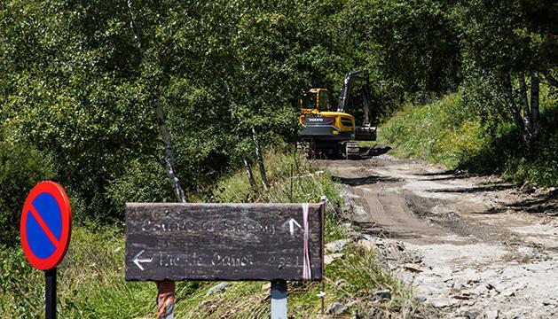 Una màquina excavadora treballa en la carretera d'accés als cortals de Sispony