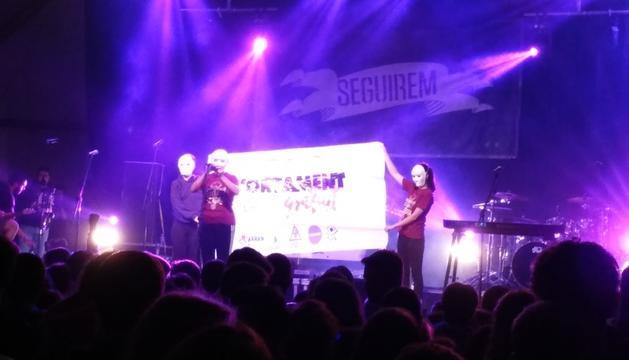Les tres activistes feministes amb una pancarta a l'escenari de la Seu.