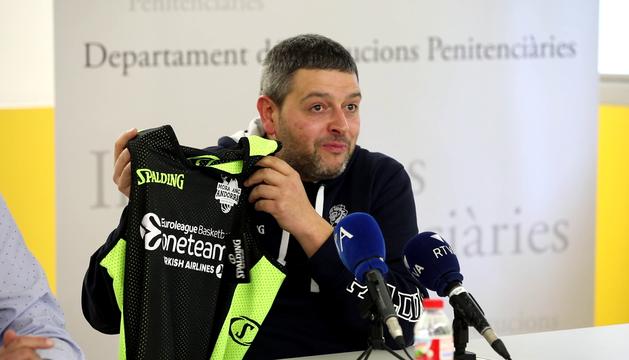 El tècnic, Jaume Tomàs, mostra la samarreta amb la què juguen els interns