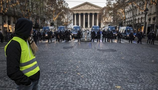Un dels manifestants observa un dispositiu policial, ahir al centre de París.