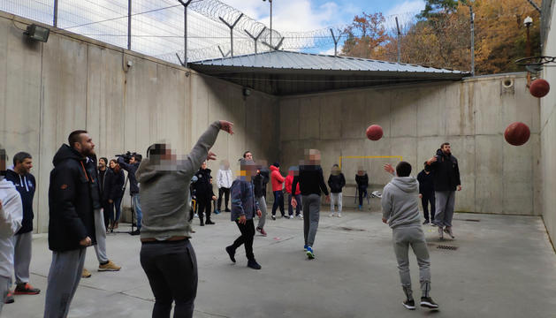 Els jugadors del MoraBanc formant parelles amb els interns al pati del centre.