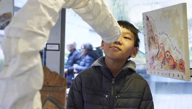 Una de les obres exposades, atentament observada per un nen.