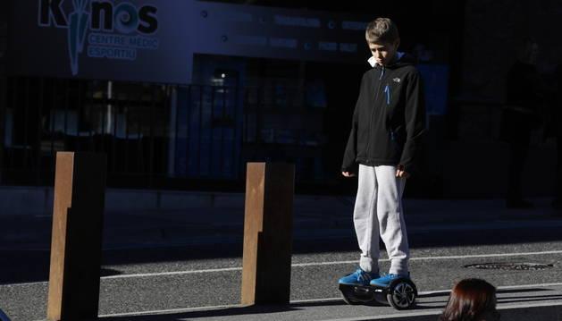Un nen circulant amb un patinet elèctric.