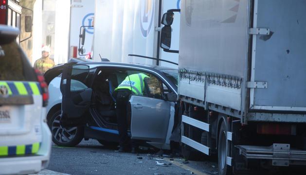 Un agent de policia inspeccionant l'interior del vehicle sinistrat.