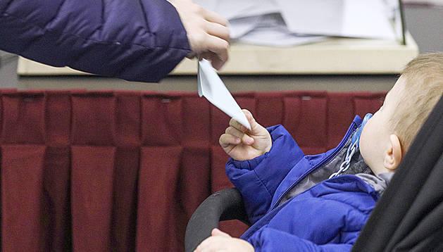 Un nadó subjecta un sobre durant les votacions de diumenge passat a Escaldes-Engordany.