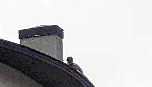 A la foto es veu l'home caminant nu per la teulada.