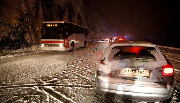 Un autobús interurbà circulant durant una nevada.