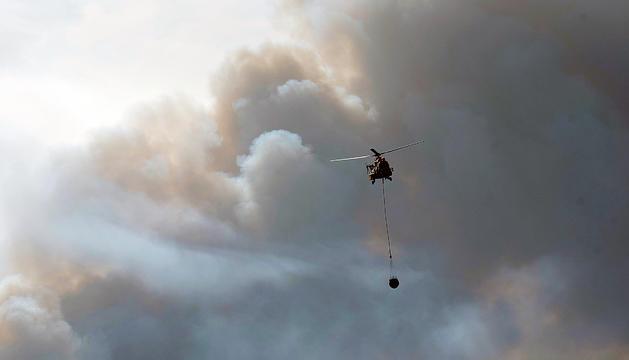 Un helicòpter treballa en les tasques d'extinció del foc a la Ribera d'Ebre, ahir.