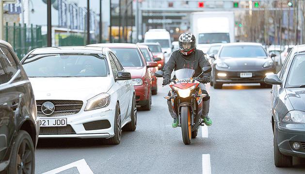 Una motocicleta circula entre cotxes al país.